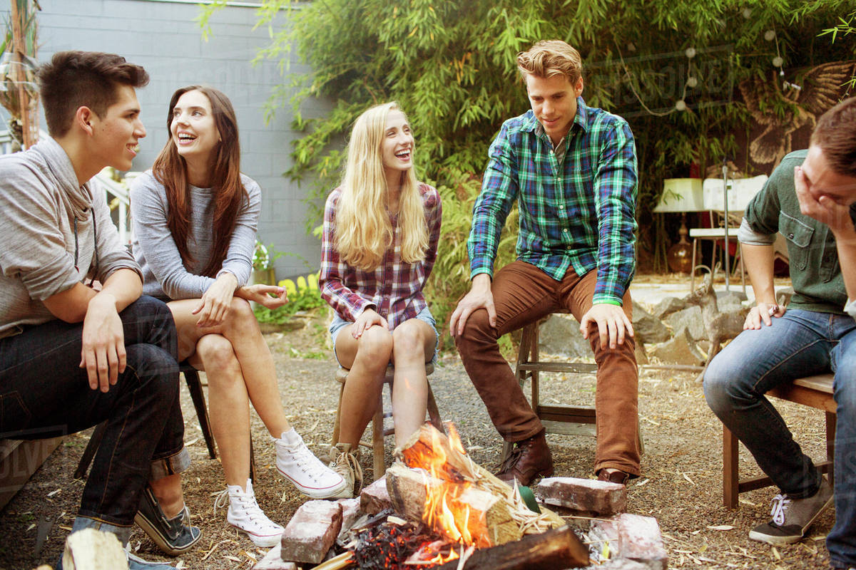 Teenage girl (16-17) laughing with her friends by campfire Royalty-free stock photo