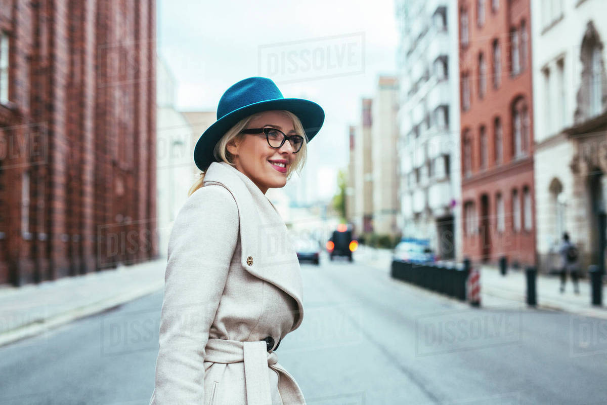 Side view of happy woman looking away while standing on city street stock  photo