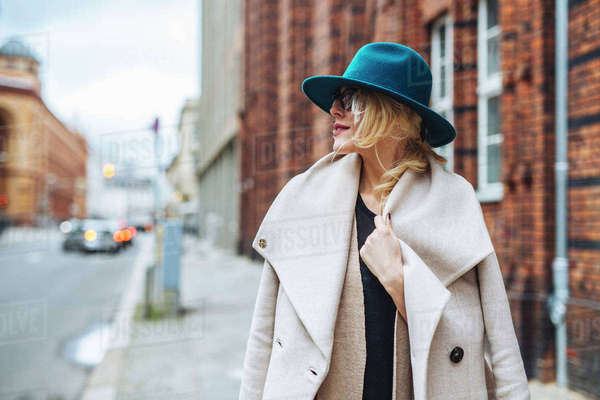 Woman wearing coat looking away while standing on footpath in city Royalty-free stock photo