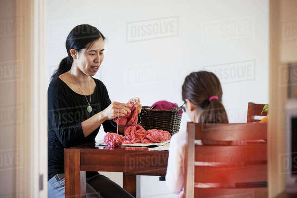 Mother and daughter knitting wool while sitting at table Royalty-free stock photo