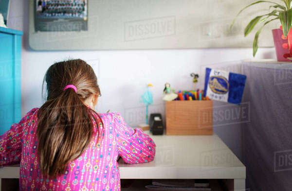 Rear view of girl studying at table Royalty-free stock photo
