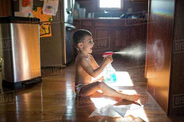 Side view of boy spraying water on wooden cupboard while sitting on floor at home Royalty-free stock photo