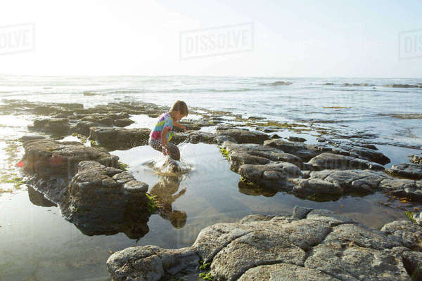 Playful boy jumping in sea against clear sky Royalty-free stock photo
