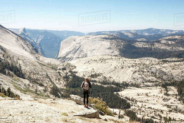Rear view of hiker standing on mountain on sunny day Royalty-free stock photo