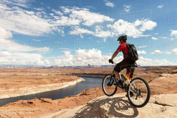 Mountain biker with bicycle standing on rock formation against cloudy sky Royalty-free stock photo