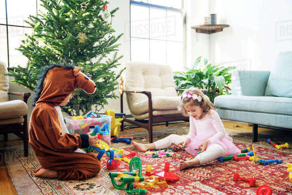 Siblings playing with building blocks while sitting by Christmas tree at home Royalty-free stock photo
