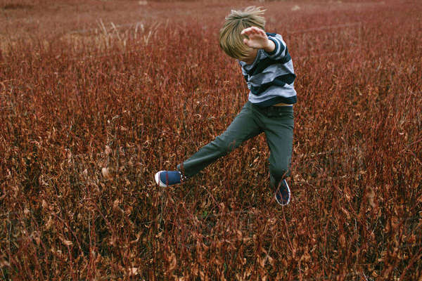 Full length of boy jumping on field Royalty-free stock photo