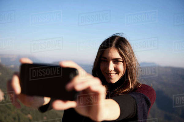 Woman taking selfie while standing against sky Royalty-free stock photo