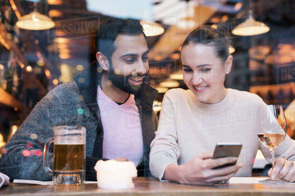 Woman with boyfriend using mobile phone seen through restaurant window Royalty-free stock photo