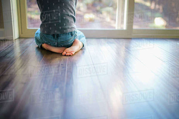 Low section of girl kneeling on hardwood floor by window at home Royalty-free stock photo