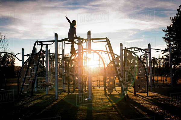 Girl playing on metallic structure at park against cloudy sky Royalty-free stock photo