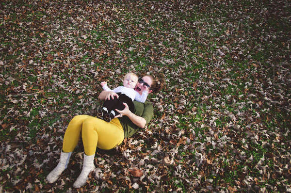 High angle view of woman with baby girl lying on dry leaves at field Royalty-free stock photo