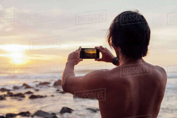 Rear view of man photographing at beach against sky Royalty-free stock photo