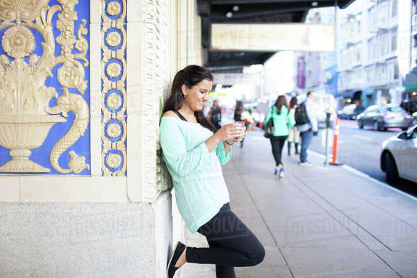 Woman using smart phone while leaning on wall at footpath Royalty-free stock photo