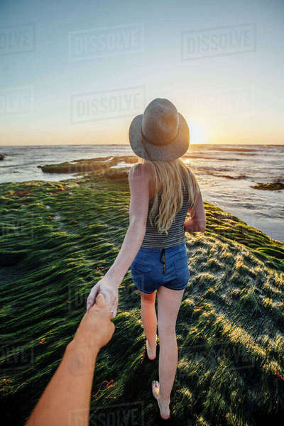 Cropped hand of man holding girlfriend's hand while walking on grass at beach during sunset Royalty-free stock photo