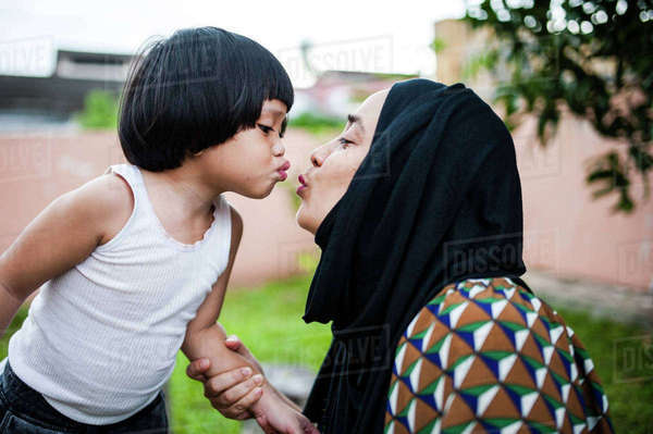 Playful mother and daughter puckering lips in backyard Royalty-free stock photo