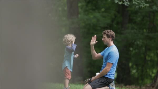 Side view of father and son giving high-five while relaxing at yard Royalty-free stock video
