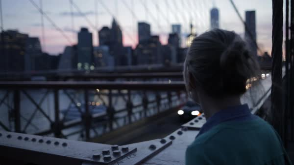 Rear view of woman looking at cityscape while standing on Brooklyn Bridge during dusk Royalty-free stock video
