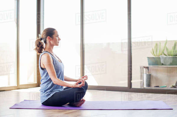 Side view of woman practicing yoga at home Royalty-free stock photo