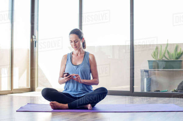 Woman using smart phone while sitting on exercise mat at home Royalty-free stock photo