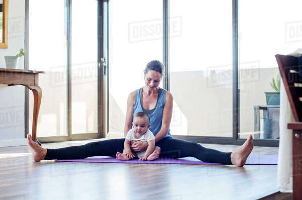 Mother holding baby boy while exercising at home Royalty-free stock photo