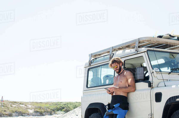 Man using mobile phone by off-road vehicle against clear sky during sunny day Royalty-free stock photo