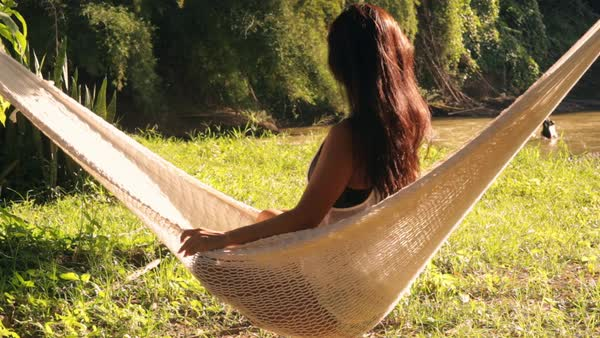 Lockdown shot of woman relaxing on hammock by river at forest Royalty-free stock video