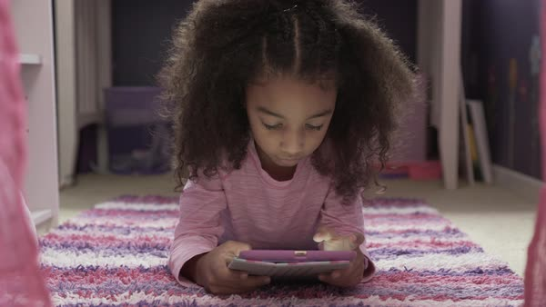 Dolly shot of girl using tablet computer while lying on rug at home Royalty-free stock video
