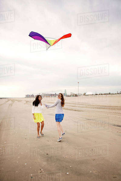Two girlfriends (16-17) flying kite on beach Royalty-free stock photo