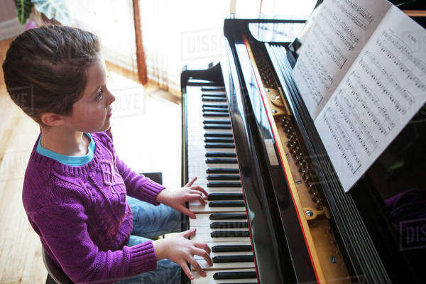 Girl (8-9) playing piano in living room Royalty-free stock photo