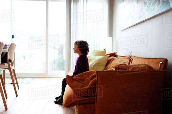 Side view of girl looking away while relaxing on sofa at home Royalty-free stock photo