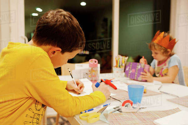 Boy writing homework while sister making craft at table Royalty-free stock photo
