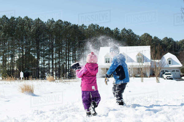 Siblings playing with snow on field against clear sky Royalty-free stock photo