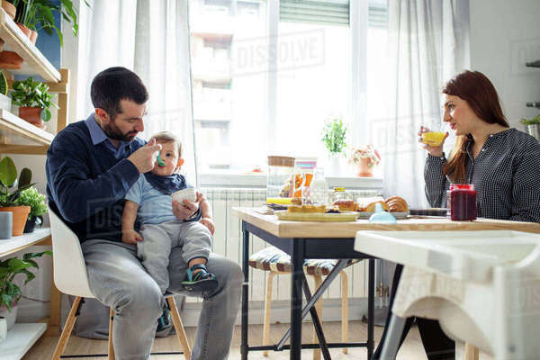 Woman looking at husband feeding son at table in kitchen Royalty-free stock photo
