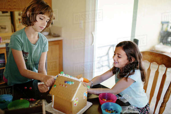 Sisters making gingerbread house at home Royalty-free stock photo
