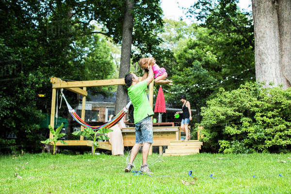 Playful father lifting daughter in backyard Royalty-free stock photo