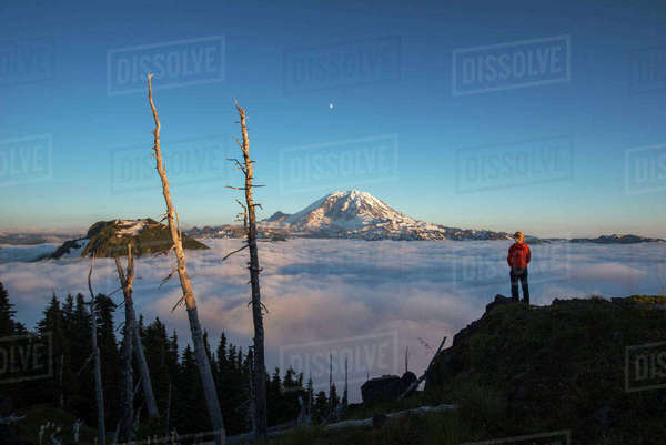 Rear view of male hiker standing on mountain by cloudscape during sunrise Royalty-free stock photo