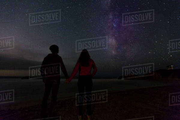 Rear view of couple holding hands while looking at starry sky at night Royalty-free stock photo
