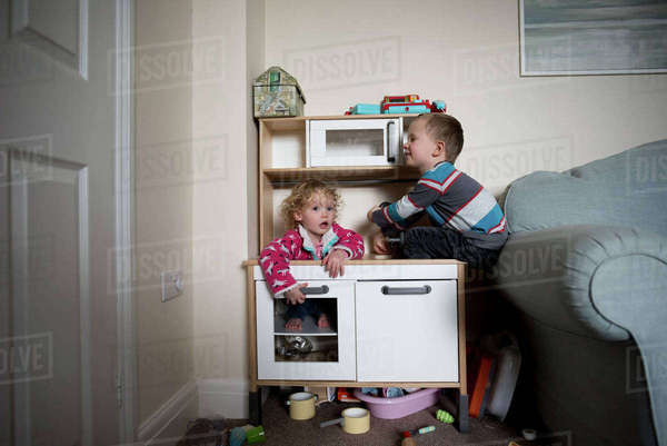 Siblings playing on cabinet by sofa at home Royalty-free stock photo