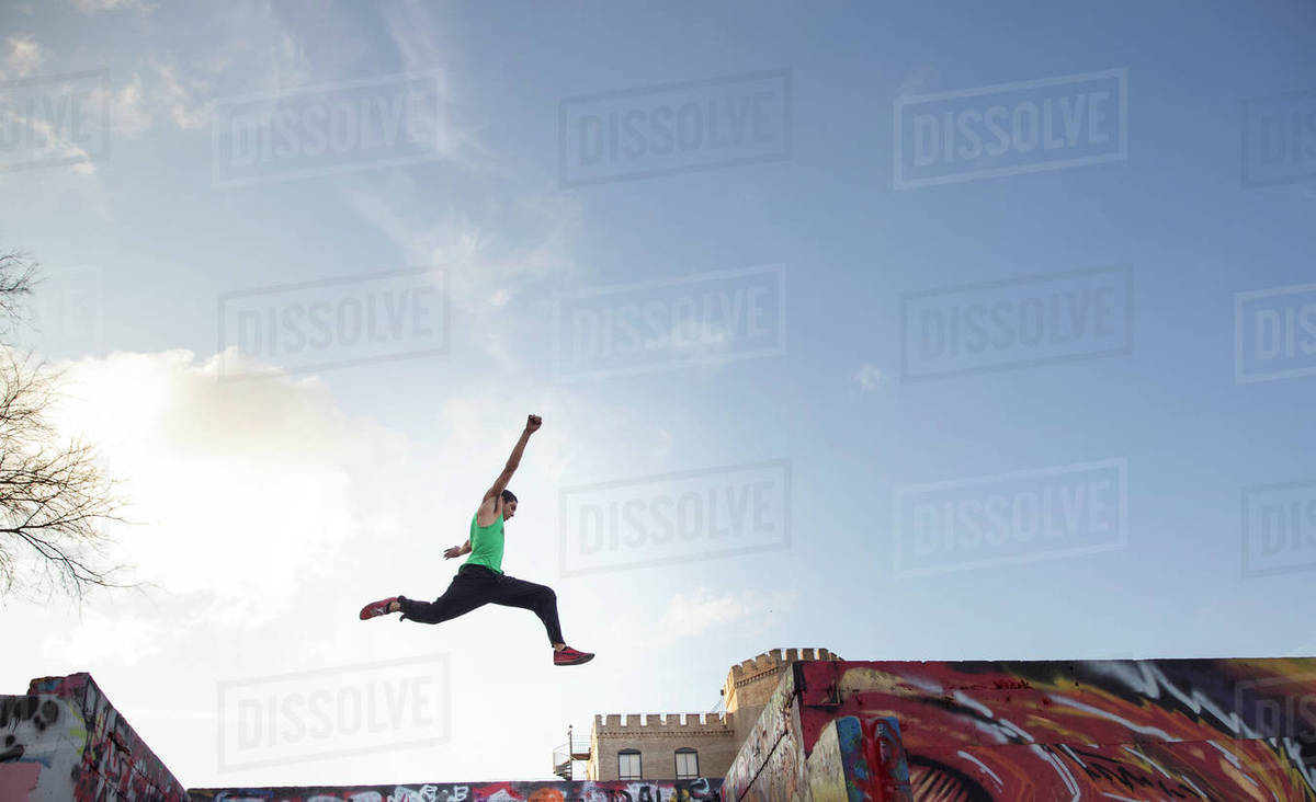 Low angle view of stunt man jumping over buildings against sky Royalty-free stock photo