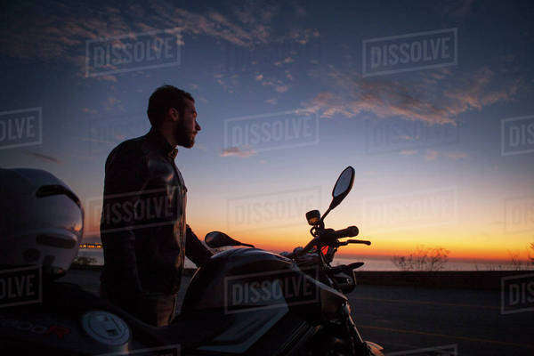 Man on motorbike by sea at sunrise Royalty-free stock photo