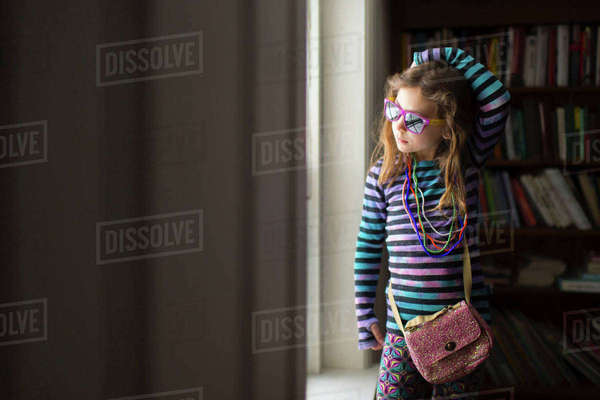 Girl wearing necklace and sunglasses standing by window at home Royalty-free stock photo