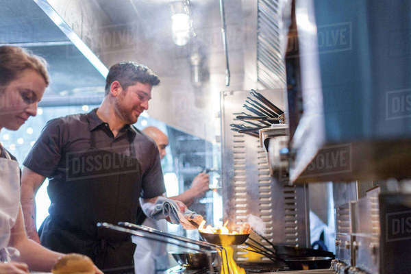 Chefs preparing food in flames in kitchen at restaurant Royalty-free stock photo