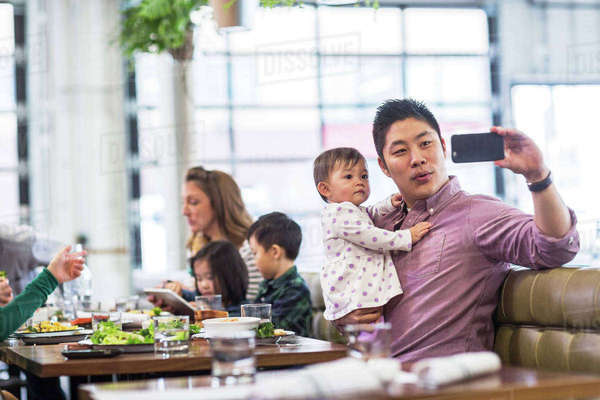 Father taking selfie with baby girl while sitting with family in restaurant Royalty-free stock photo
