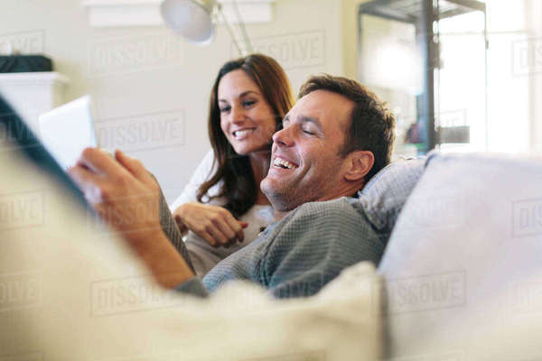 Happy couple using digital tablet while relaxing on sofa at home Royalty-free stock photo