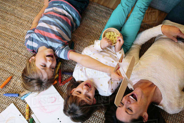 Overhead view of playful children with mother lying on carpet at home Royalty-free stock photo