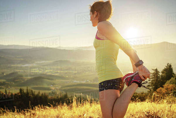 Side view of woman exercising on mountain against clear sky during sunny day Royalty-free stock photo