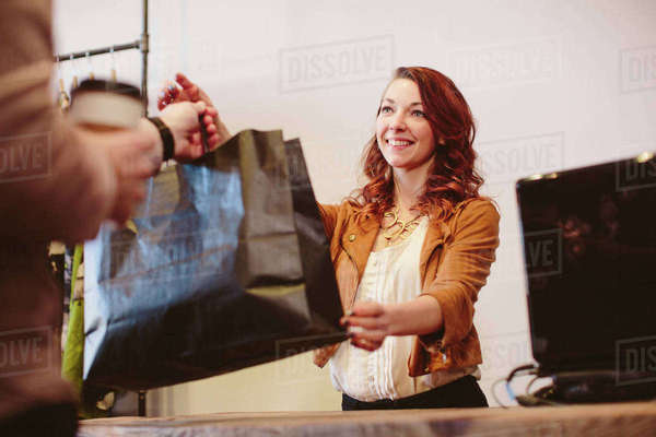 Smiling owner giving shopping bag to male customer in store Royalty-free stock photo