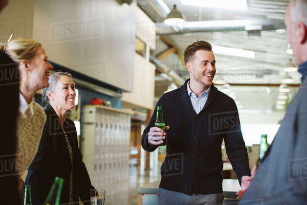 Business people talking while enjoying drinks in office Royalty-free stock photo