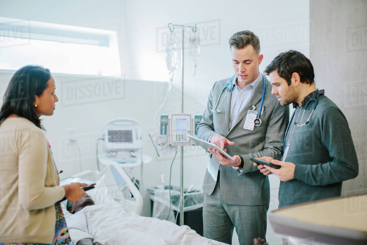 Male Doctor Training Coworkers Over Tablet Computer In Medical